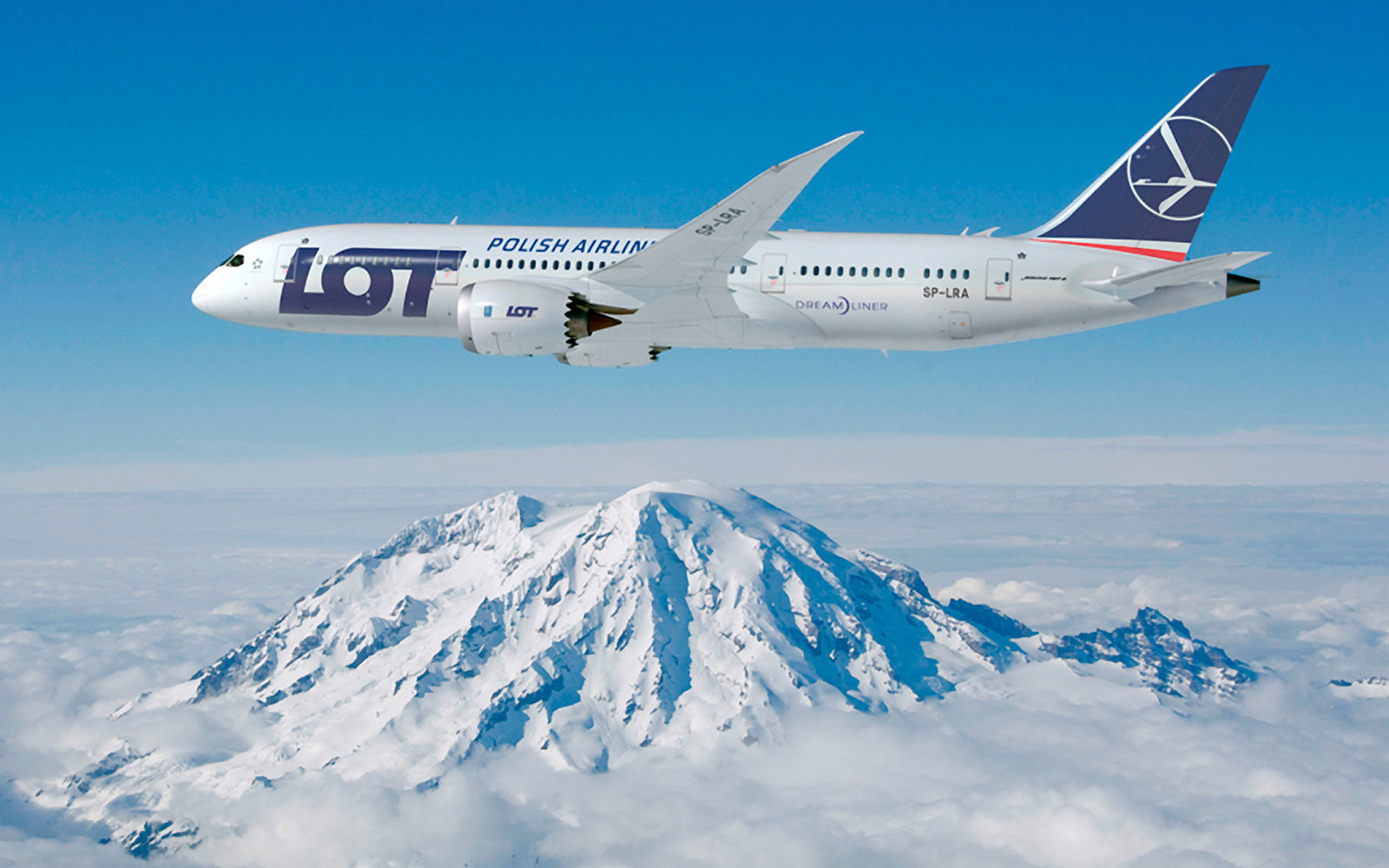 LOT Polish Airlines plane flies over a mountain