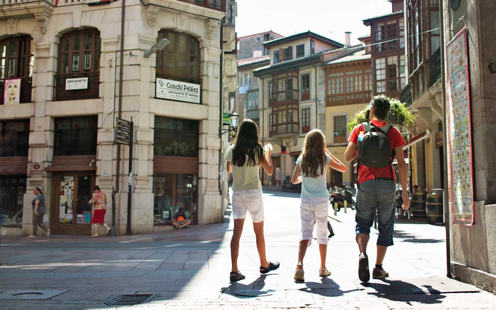 Father with his girls walking the streets of Llanes, Spain.