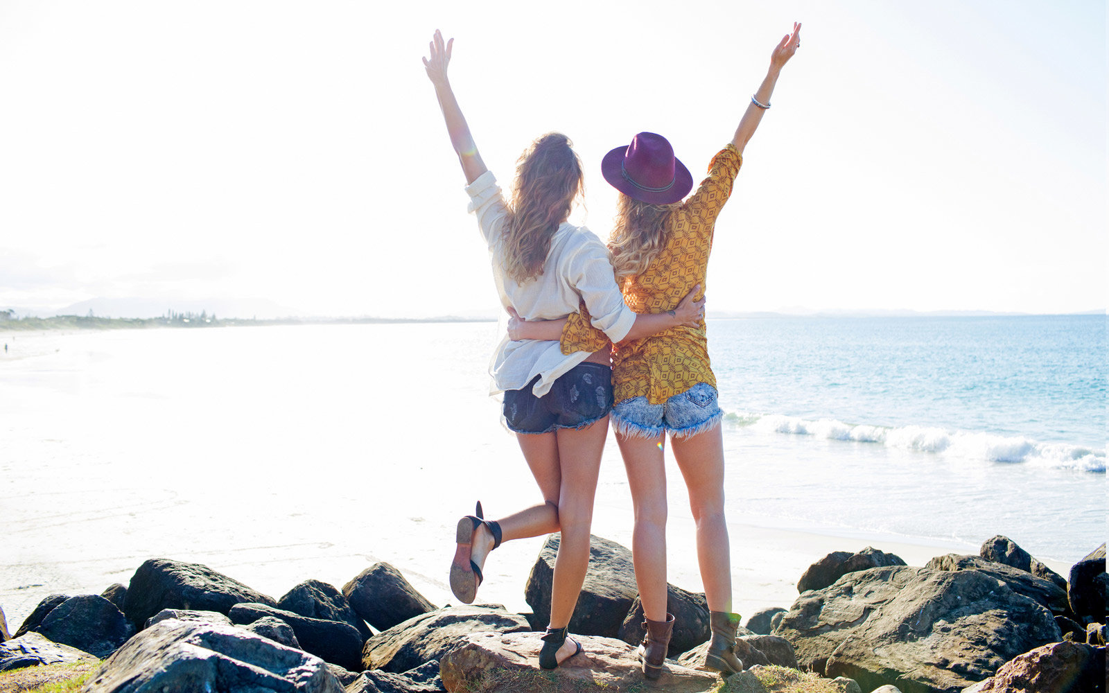 Two females arms raised on the beach