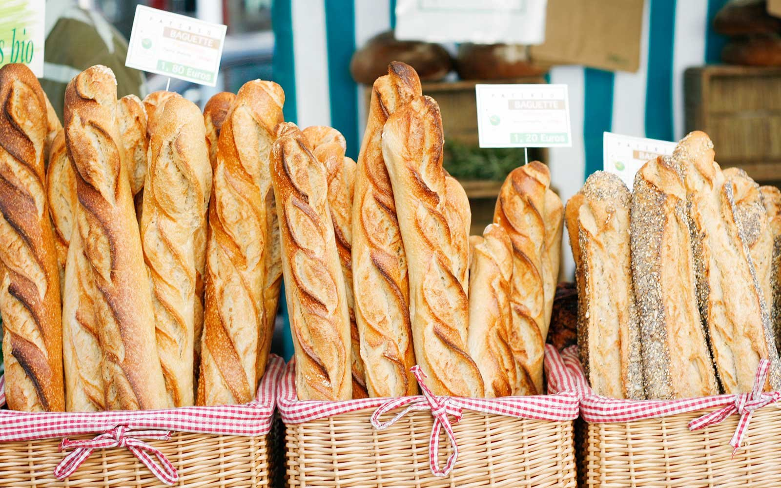 An assortment of freshly-baked baguettes on display in baskets at a farmer's market stall in Paris.