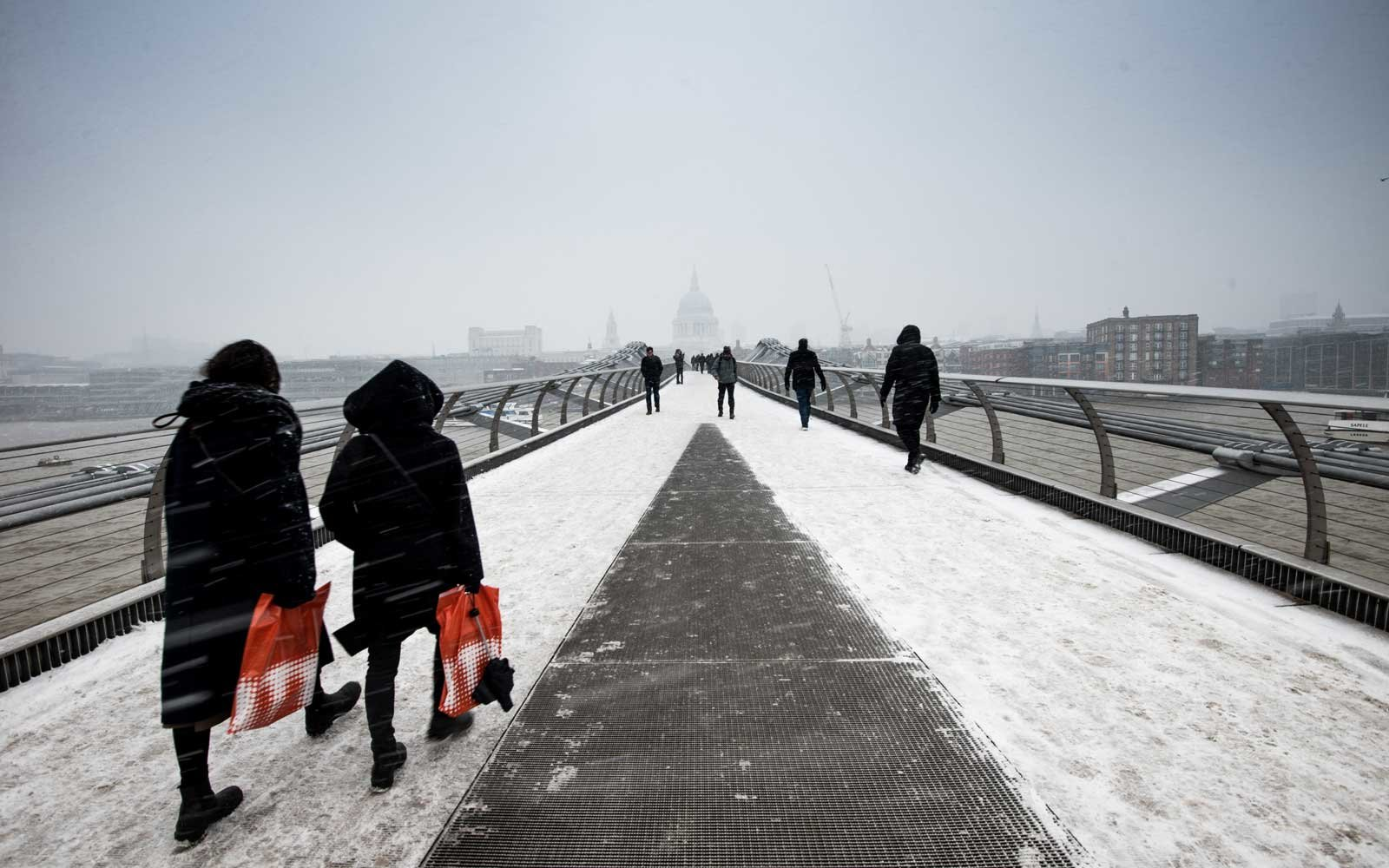People walking on Millenium Bridge under snow on March 03, 2018 in London, England.