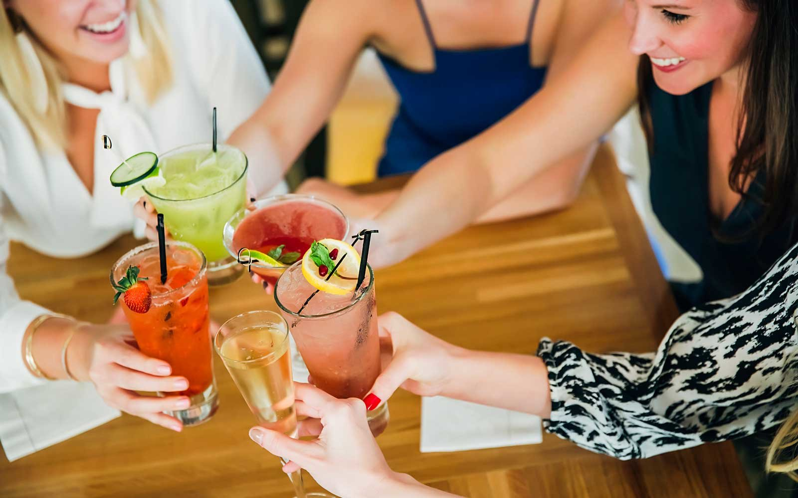 Women toasting at bar with cocktails