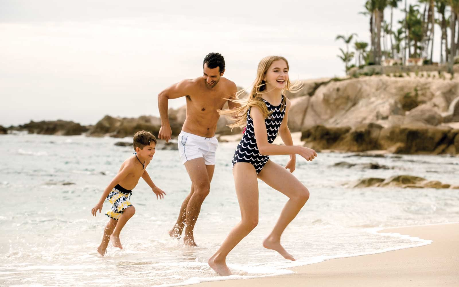 Family Running On The Beach At One Only Resorts