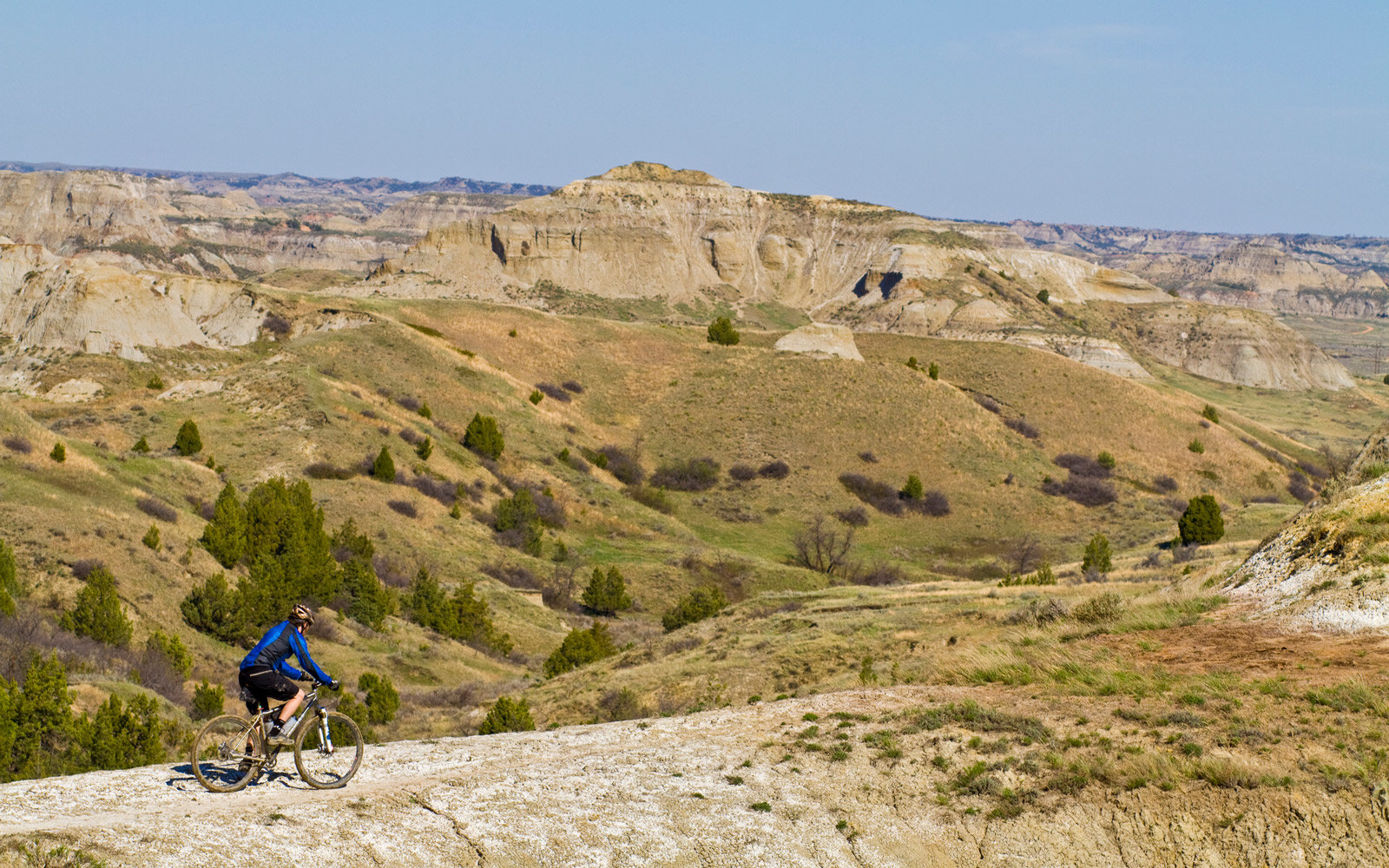 A middle aged man mountain bikes the  single track of the Maah Daah Hey Trail, North Dakota