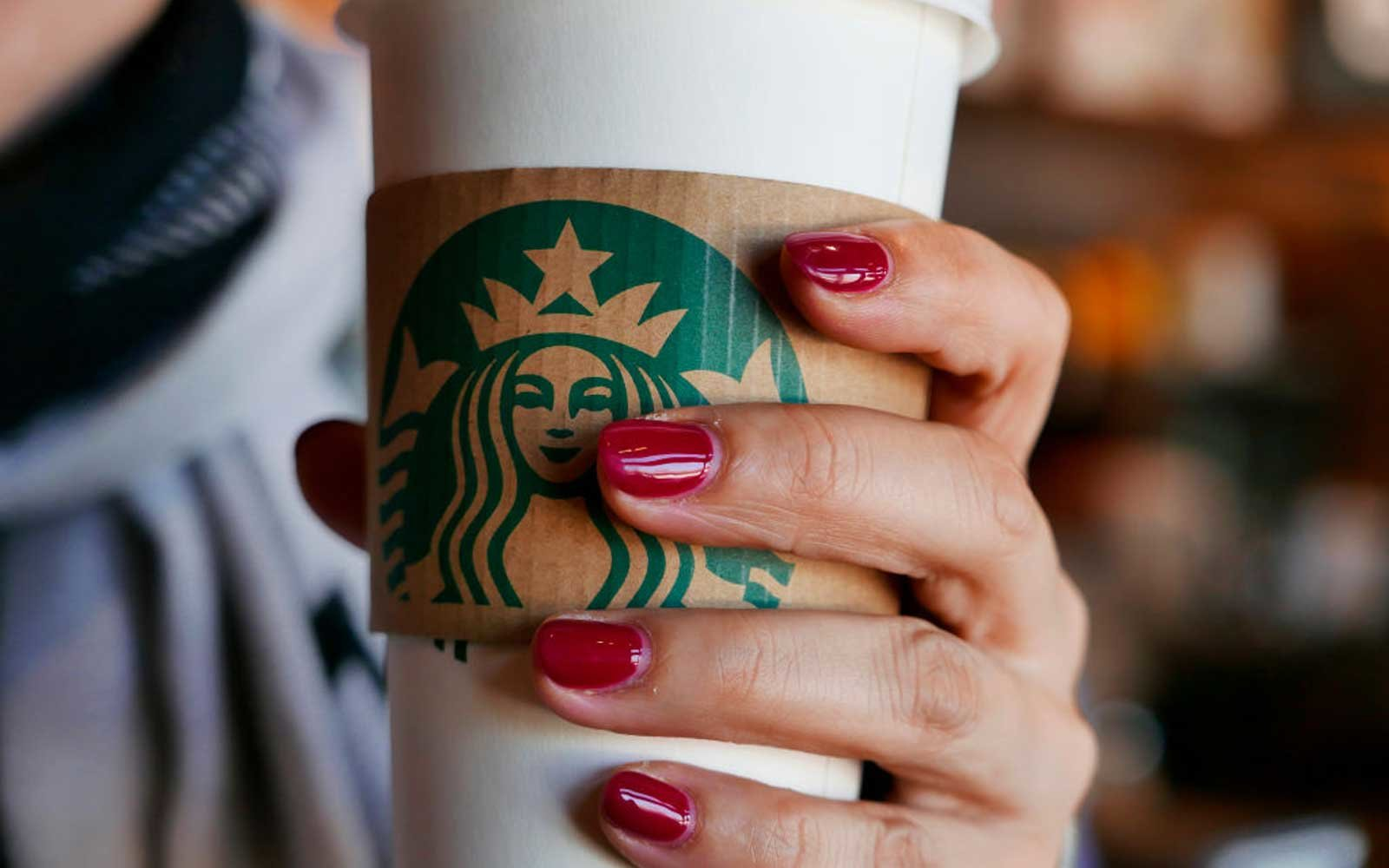 Hand holding a coffee cup in a Starbucks coffee shop.