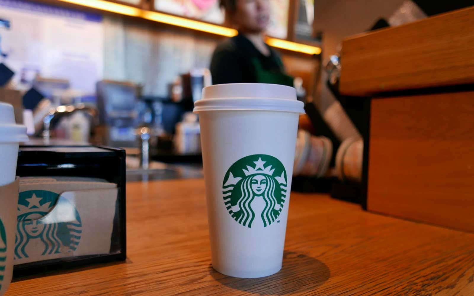 A coffee cup on the counter in a Starbucks coffee shop.  In