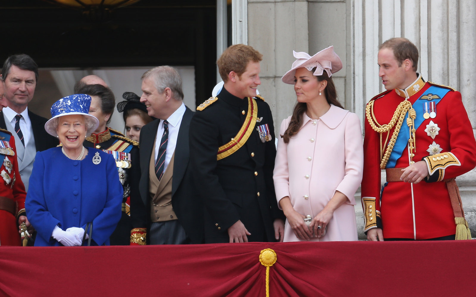 Queen Elizabeth II laughs next to Prince Harry Catherine Duchess of Cambridge and Prince William Duke of Cambridge stand on the balcony at Buckingham Palace