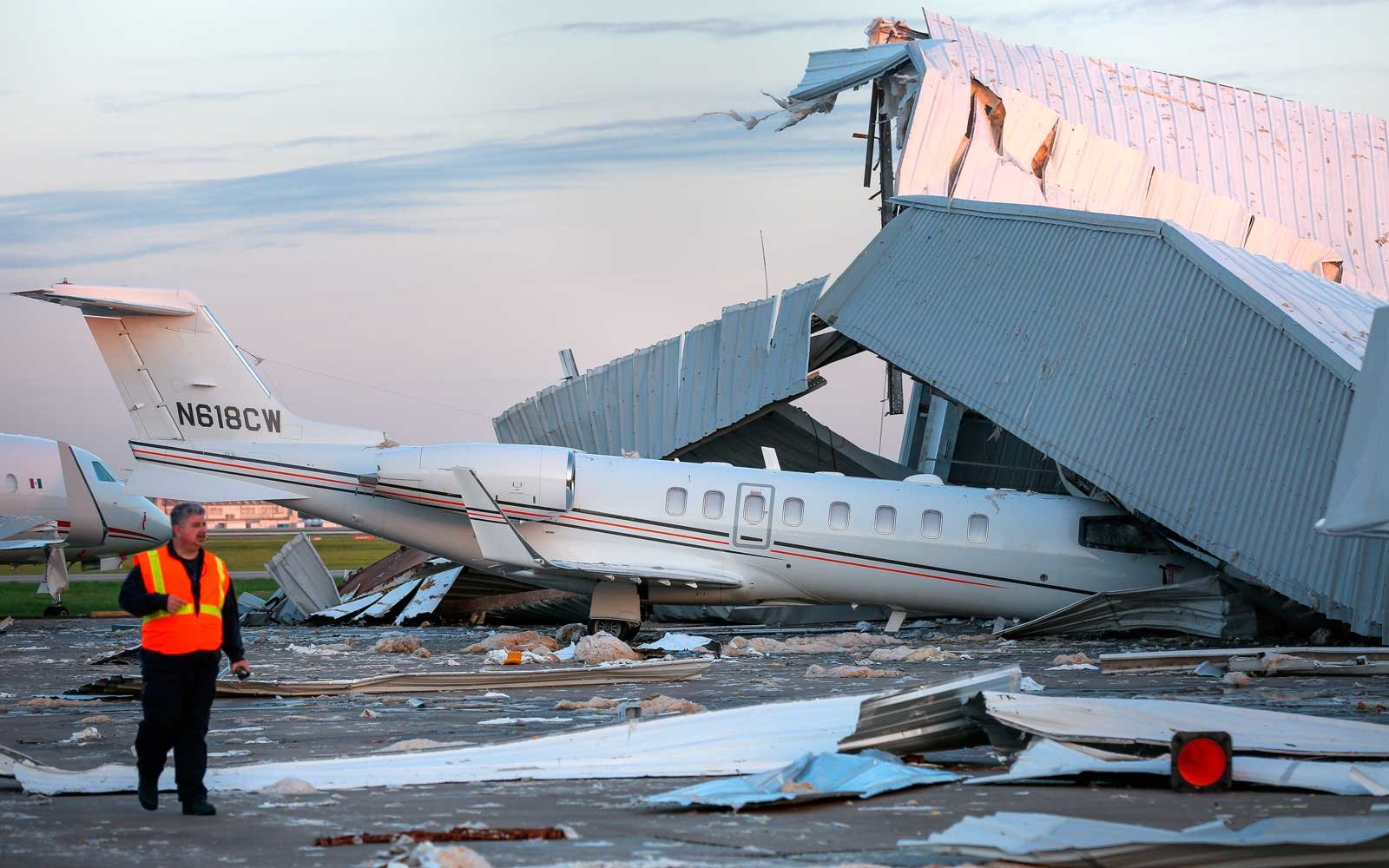Authorities look over the damage caused by winds at an airplane hangar at William P. Hobby Airport Wednesday, April 4, 2018, in Houston.