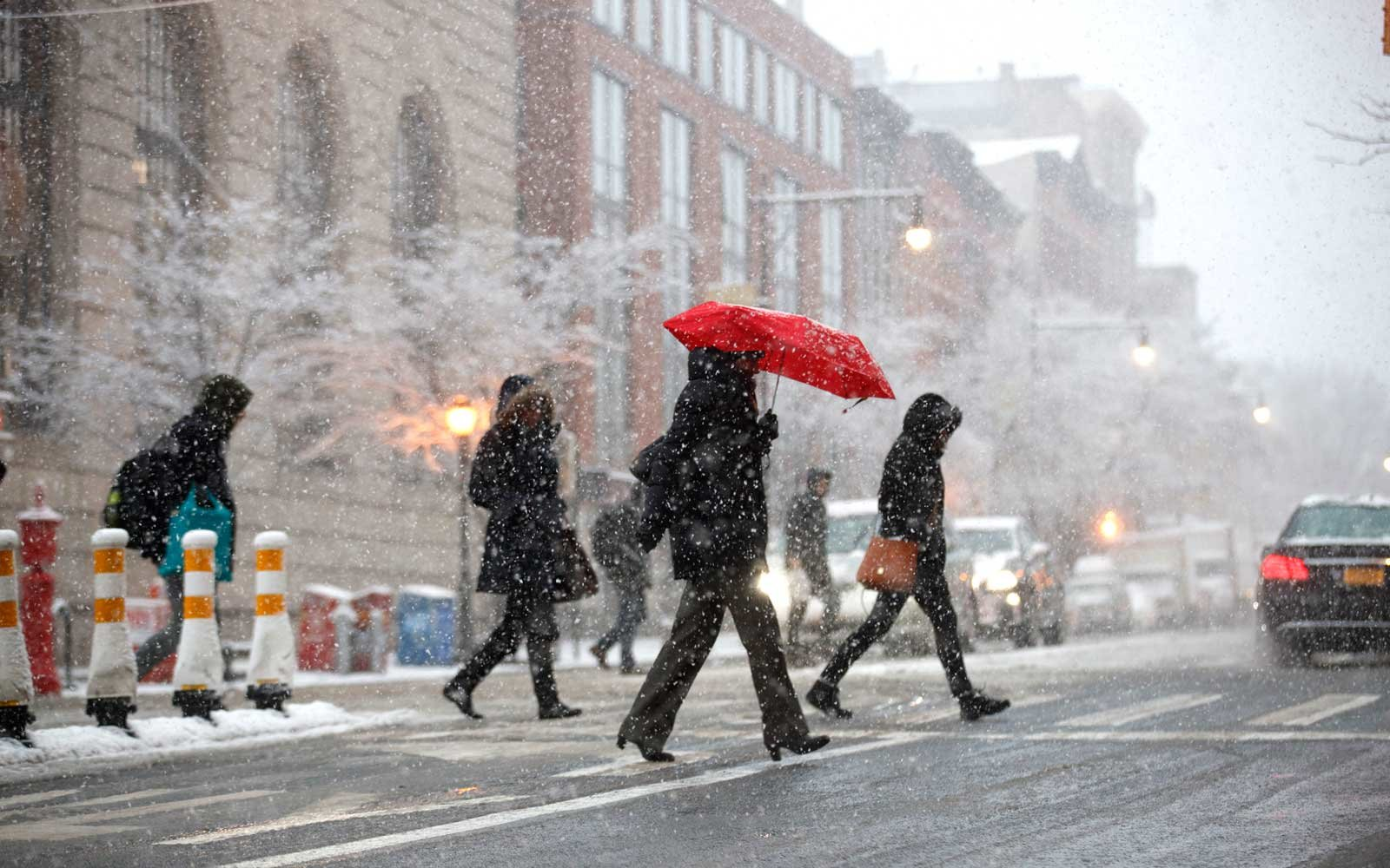 Pedestrians cross the street in the snow during the morning rush hour on Atlantic Avenue, April 2, 2018 in the Brooklyn borough of New York City.