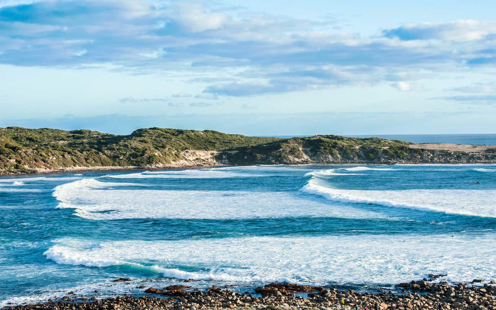 Succession of waves rolling into Cowaramup Bay with sandy headland behind