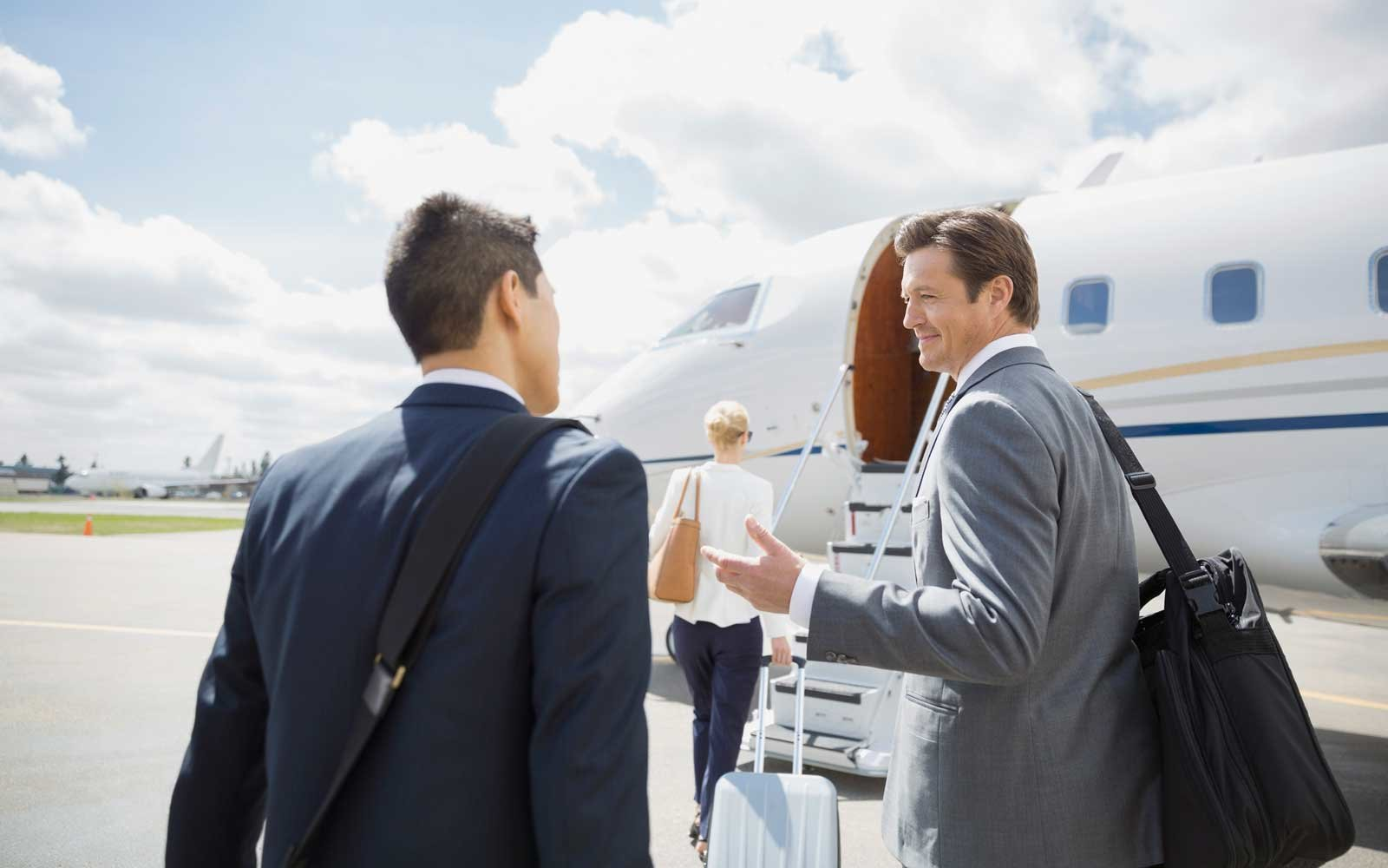 Businessmen talking on tarmac with corporate jet