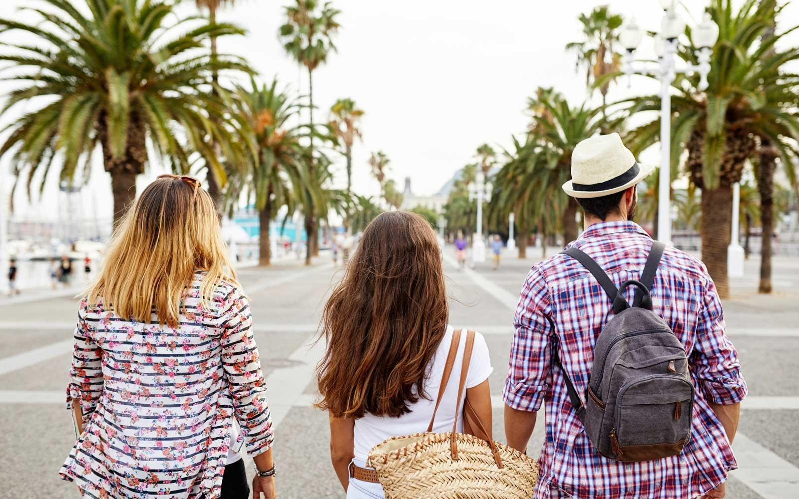 Spain, Barcelona, back view of three tourists in the city