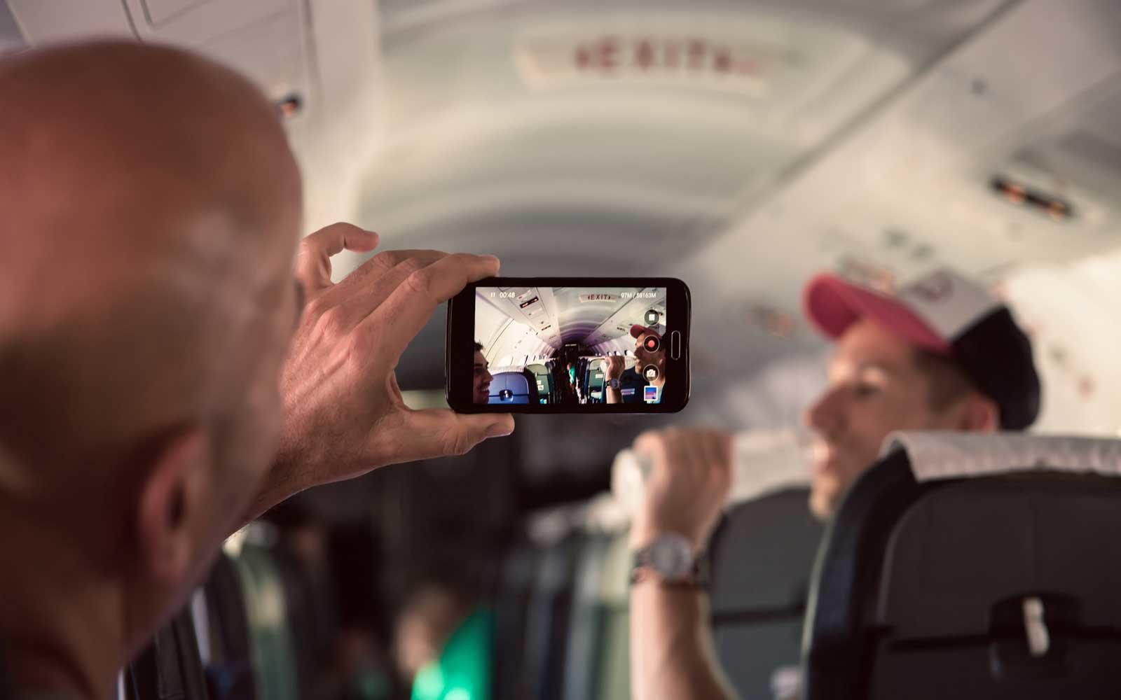 Friends taking pictures on the plane