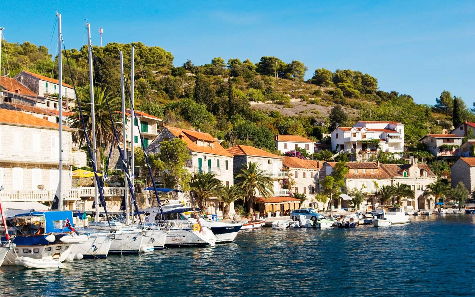 Fishing boats and charter sailboats along waterfront of Solta, Croatia