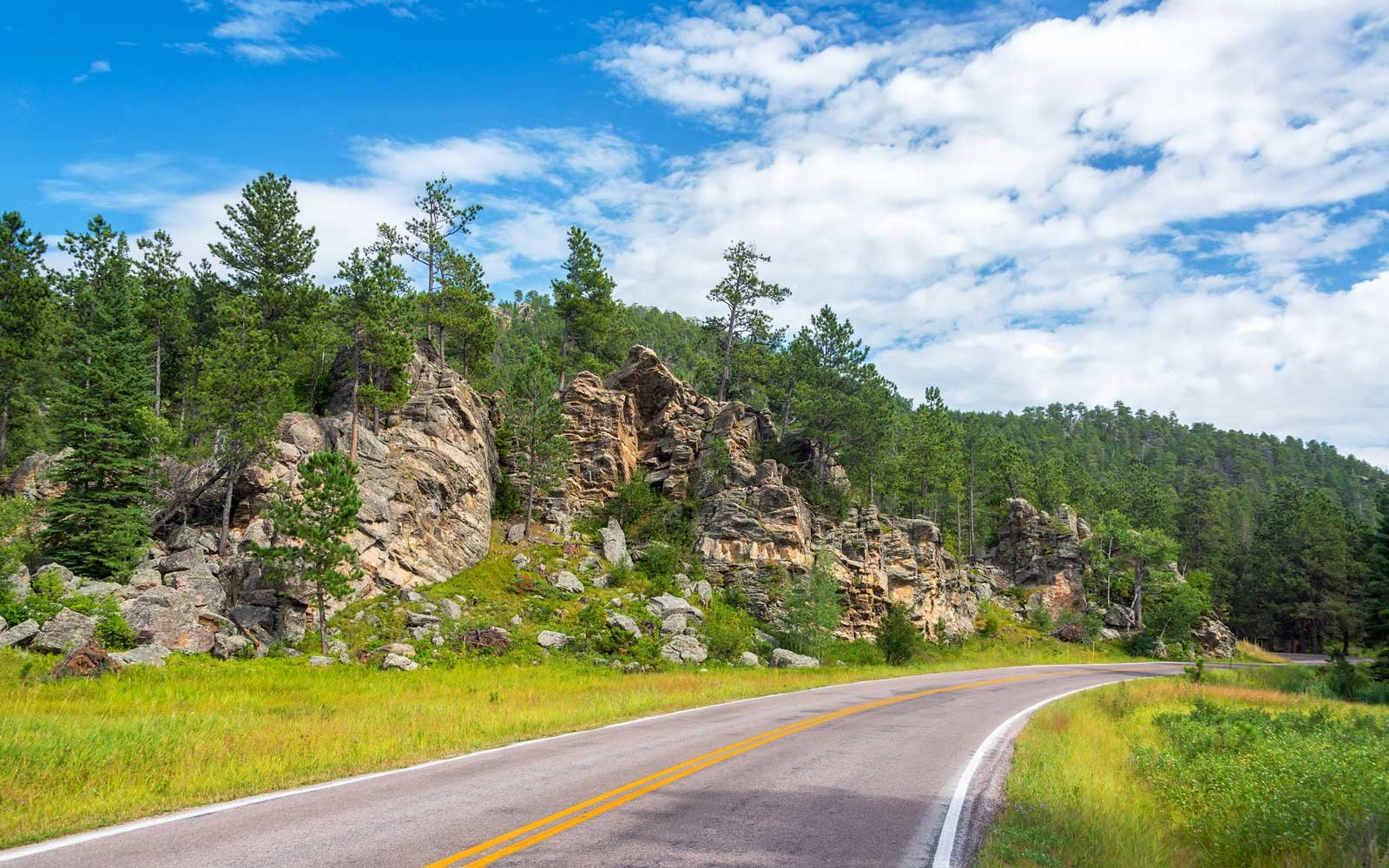 Road in Custer State Park passing beautiful rock formations in South Dakota