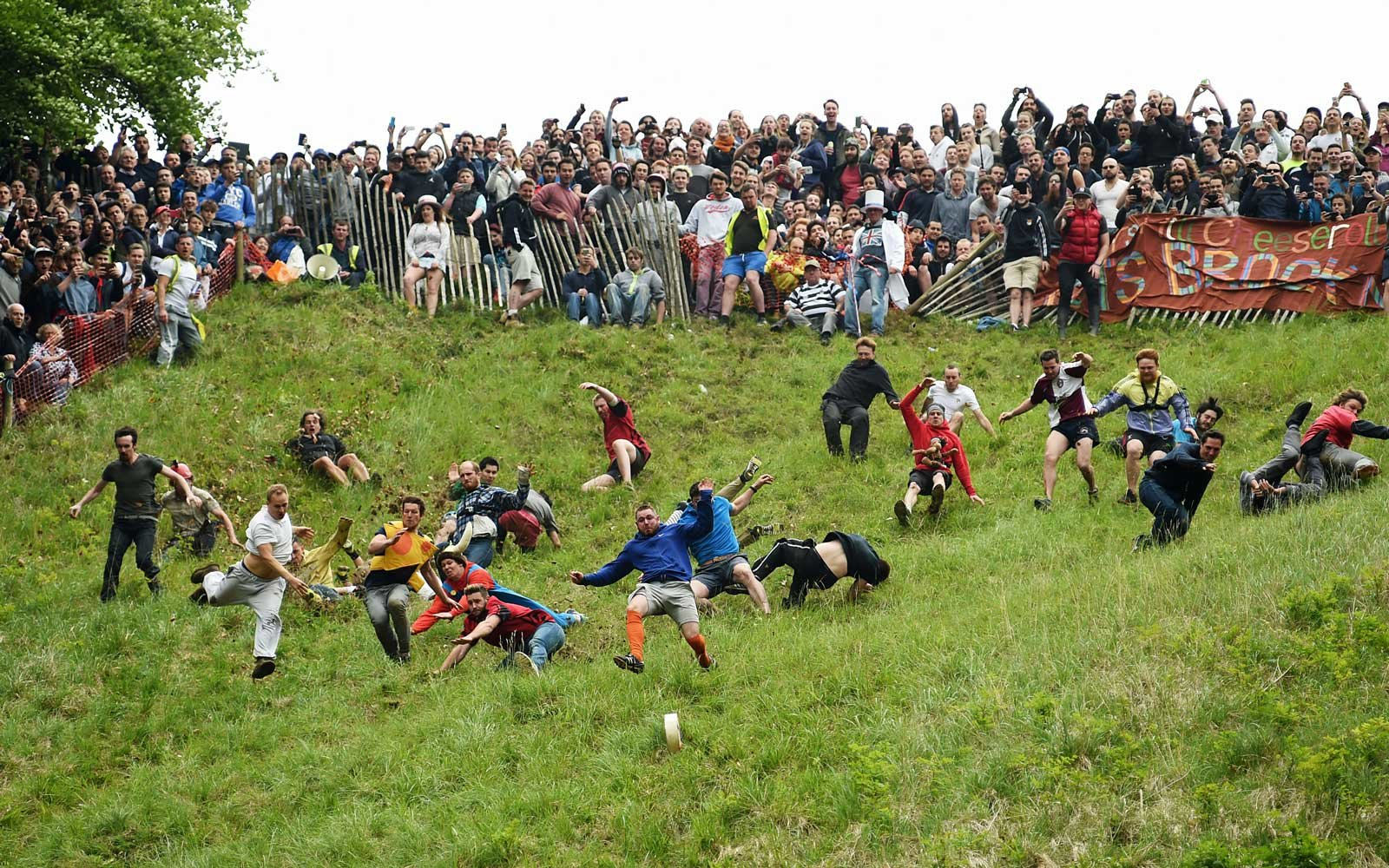 Competitors take part in the annual unofficial cheese rolling at Cooper's Hill in Brockworth, Gloucestershire