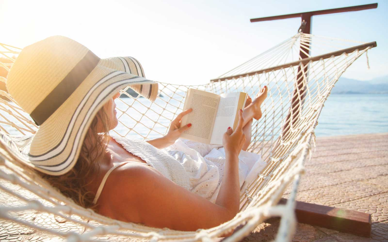 Young woman, reading a book in a hammock at sunset.