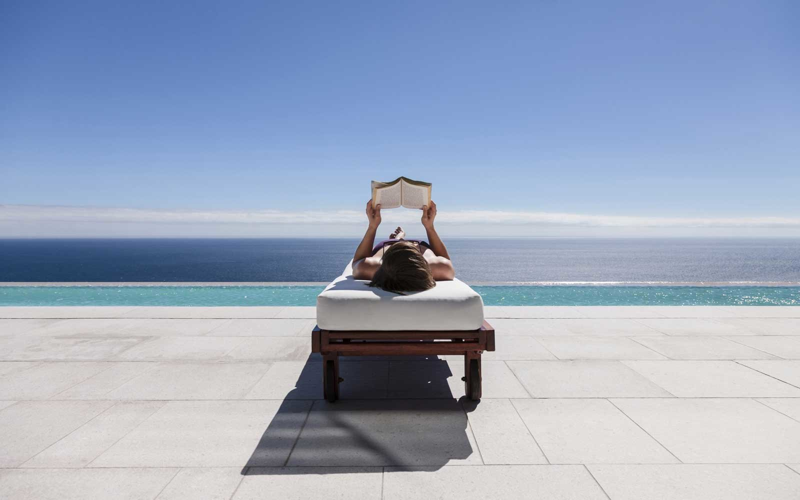 Woman reading on lounge chair at poolside overlooking the ocean