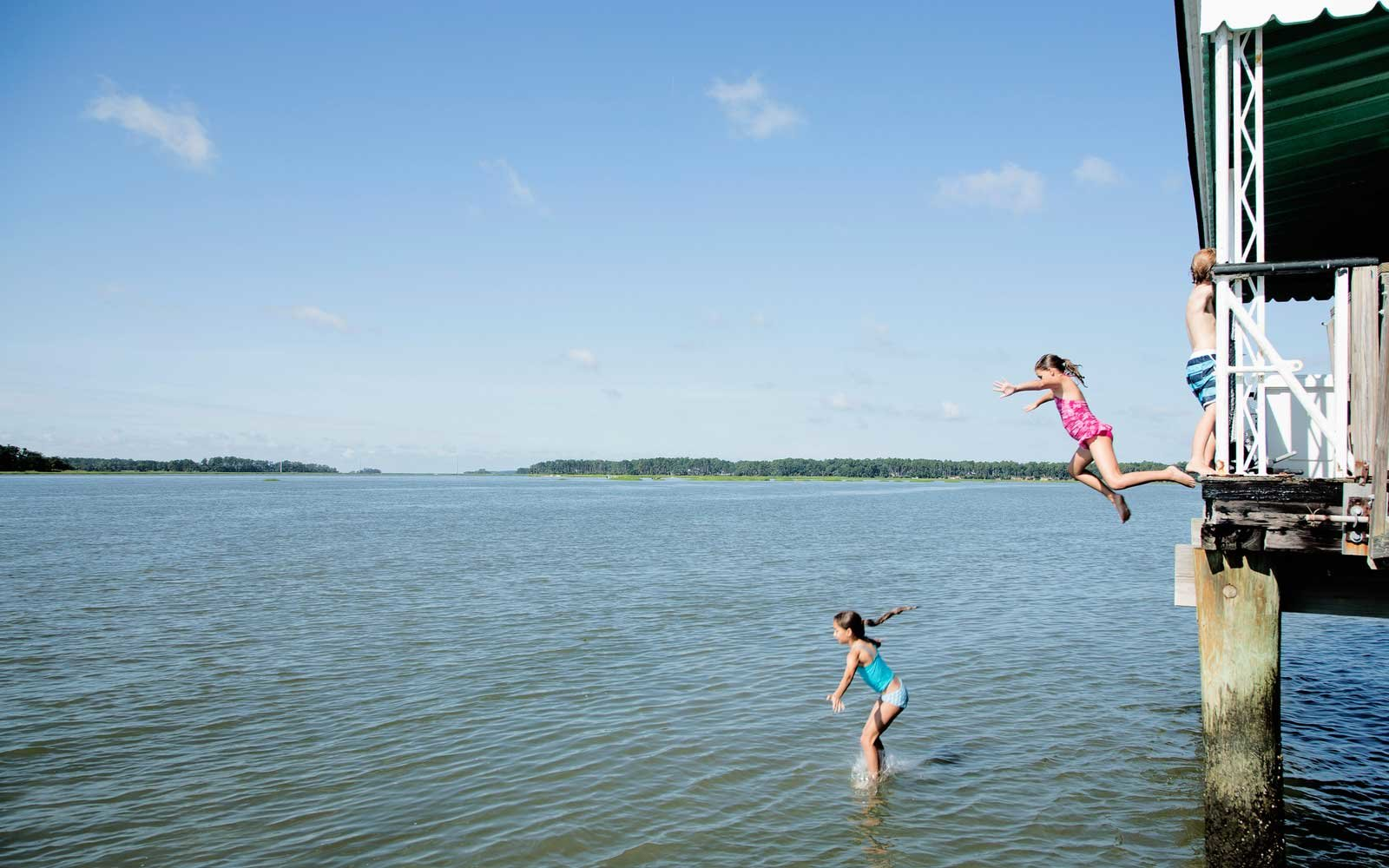 Kids jumping from dock into river
