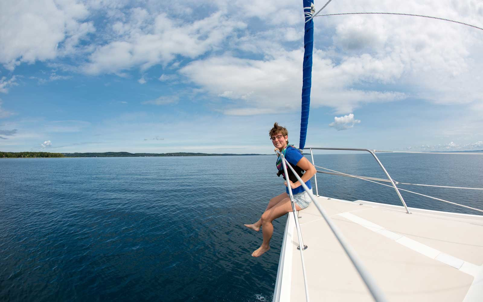 Young woman sitting on the bow of a sailboat, legs hanging over the edge on a perfect summer day in Michigan.