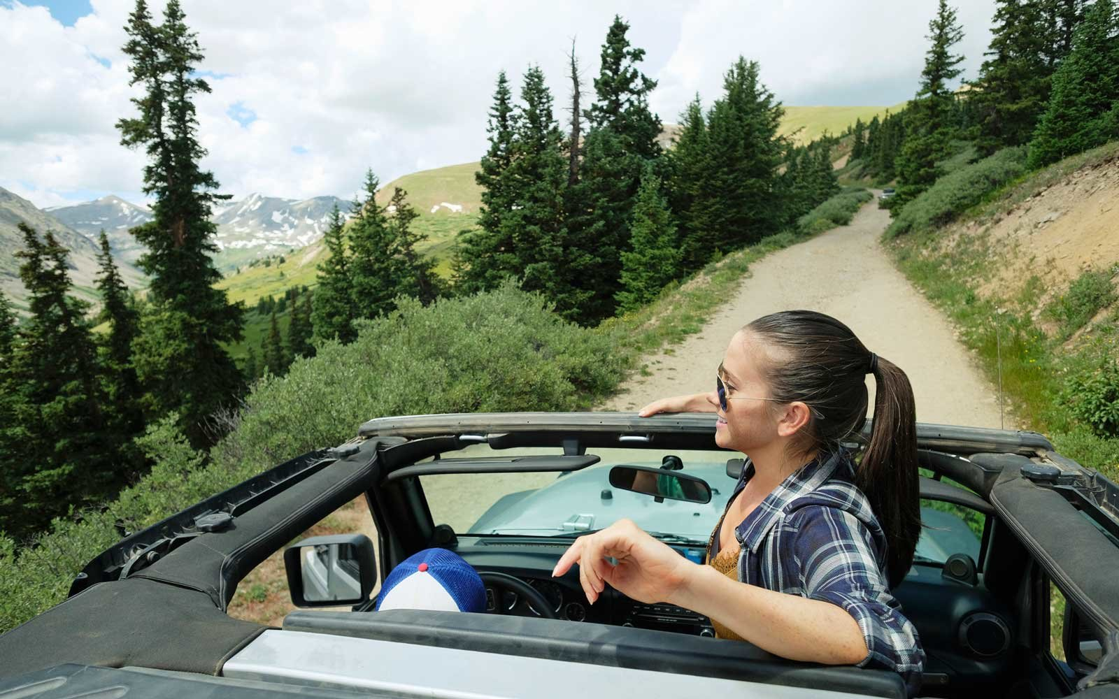 Young woman looking out from four wheel convertible in Rocky mountains, Breckenridge, Colorado