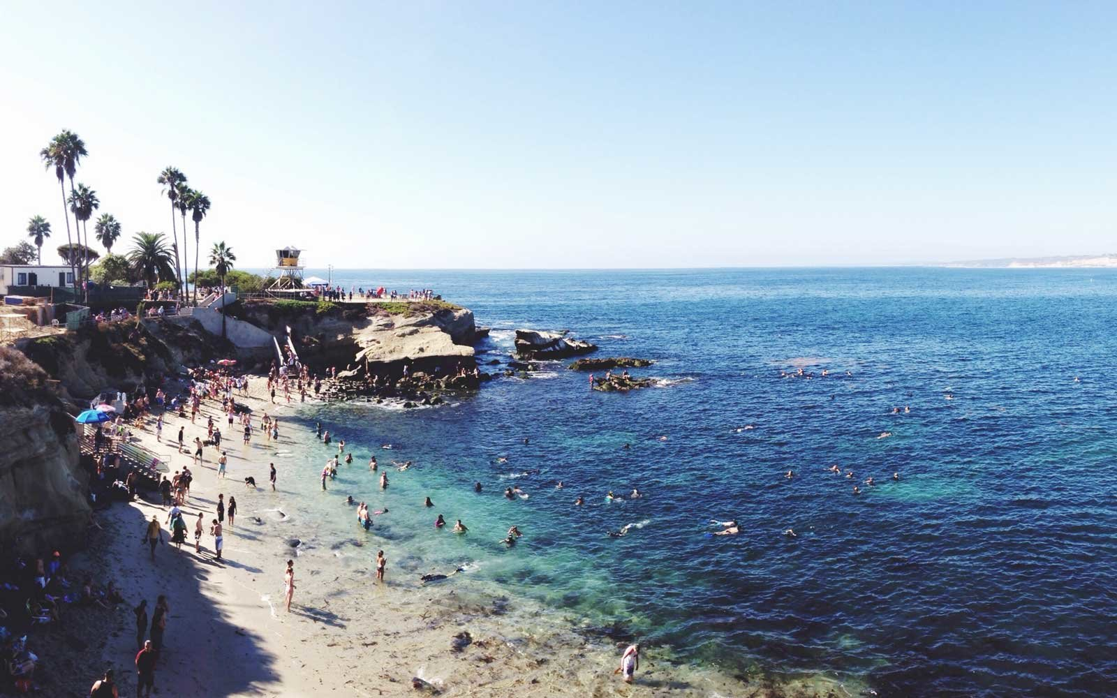 People enjoying the beach on a clear day in La Jolla, California