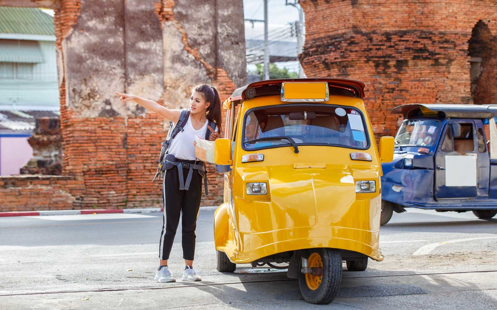 Traveler holding map travel with query for the way with tuk tuk touring