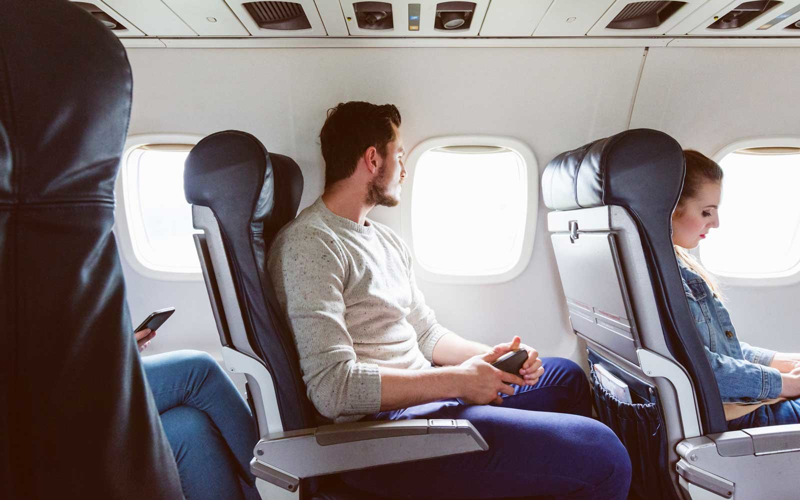 Young man sitting in airplane near window