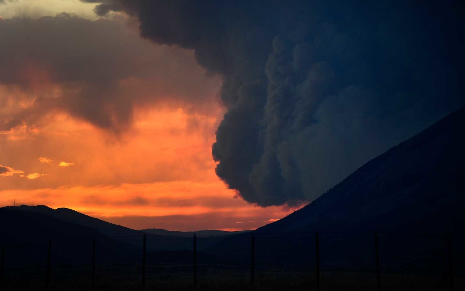 The large plume of the Spring Creek Fire is lit up by the setting sun  on July 4, 2018 in La Veta, Colorado.