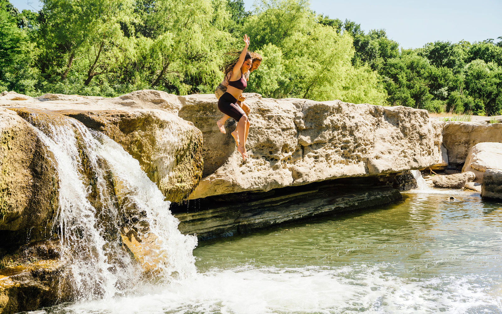 A couple jumps into a swimming hole in Austin, Texas.