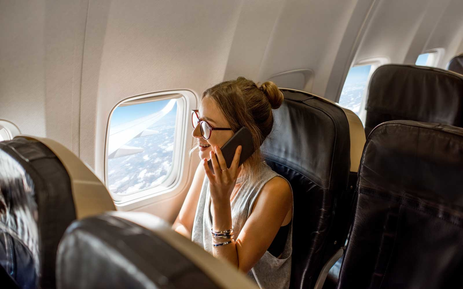 Person taking a call in the middle of flight