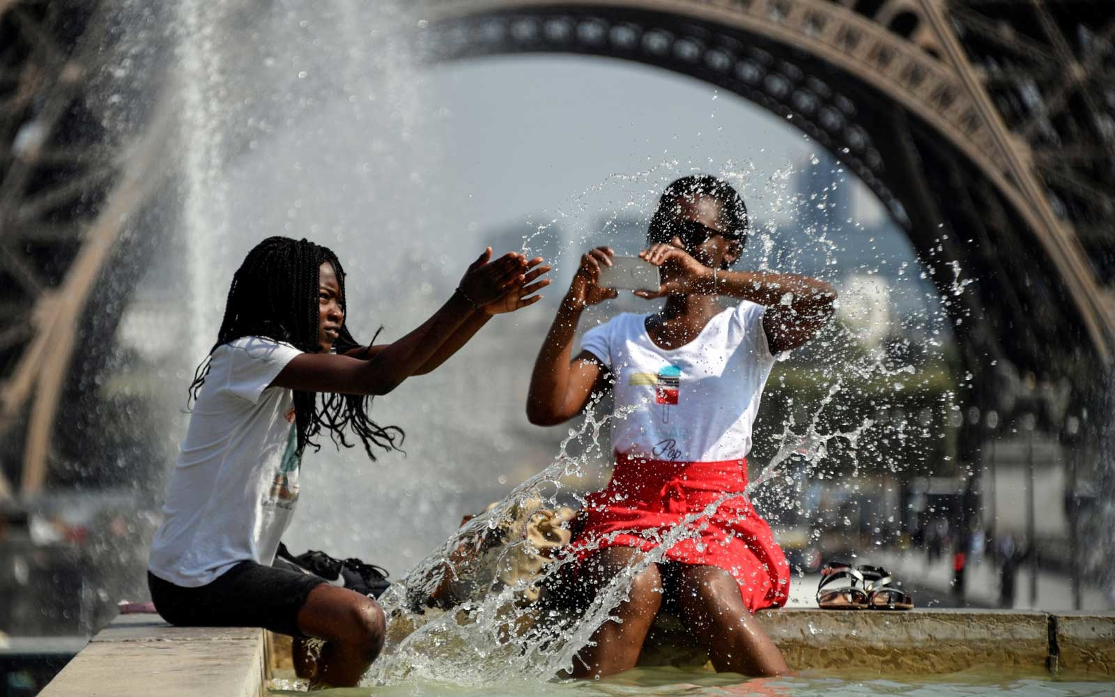 People cool themselves at the Fontaine du Trocadero in front of The Eiffel Tower in Paris on July 25, 2018
