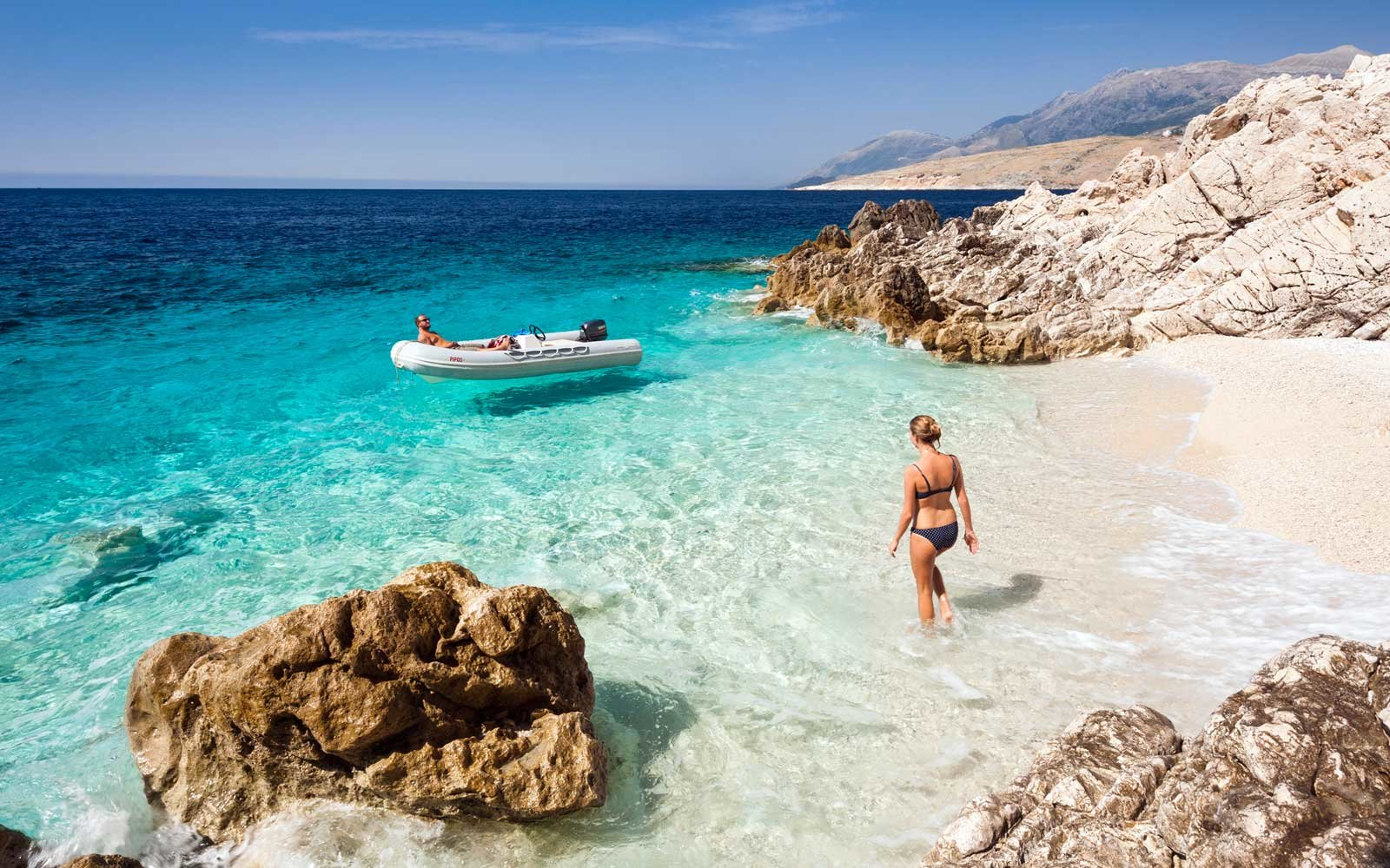 Young woman walking along a beach with a boat, Ionian Coastline south of Himara, Albania