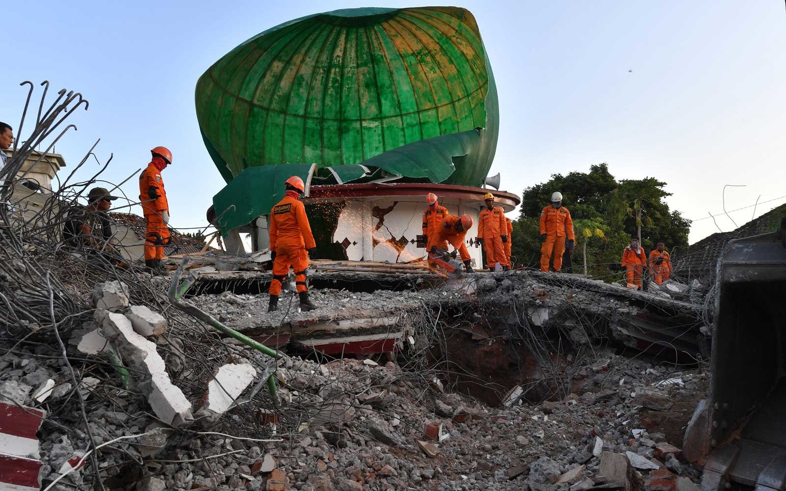 Indonesian search and rescue personnel work on a collapsed mosque in Pemenang, North Lombok on August 6, 2018