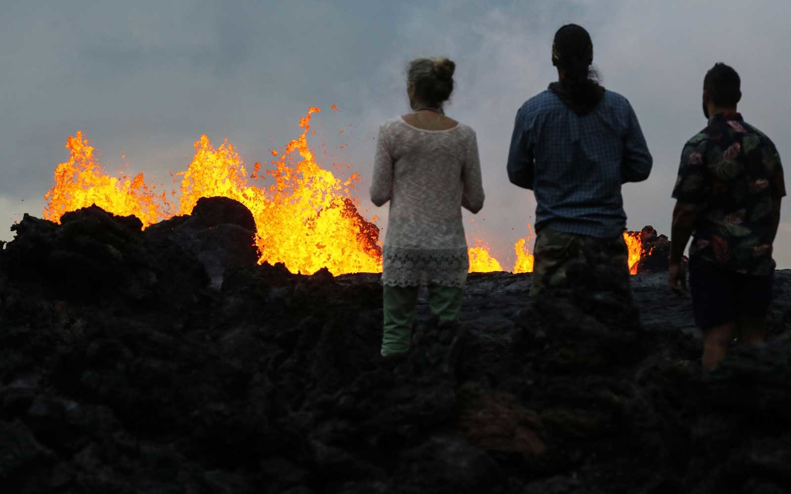 nlookers watch as lava from a Kilauea volcano fissure erupts in Leilani Estates, on Hawaii's Big Island