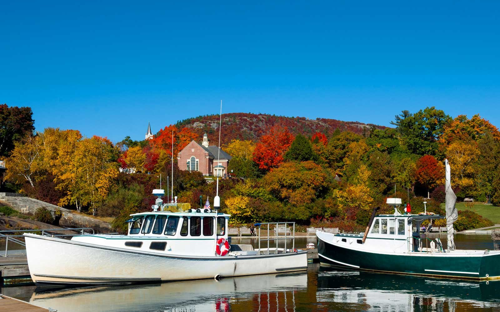 Lobster boats in Camden, Maine Harbor with fall foliage