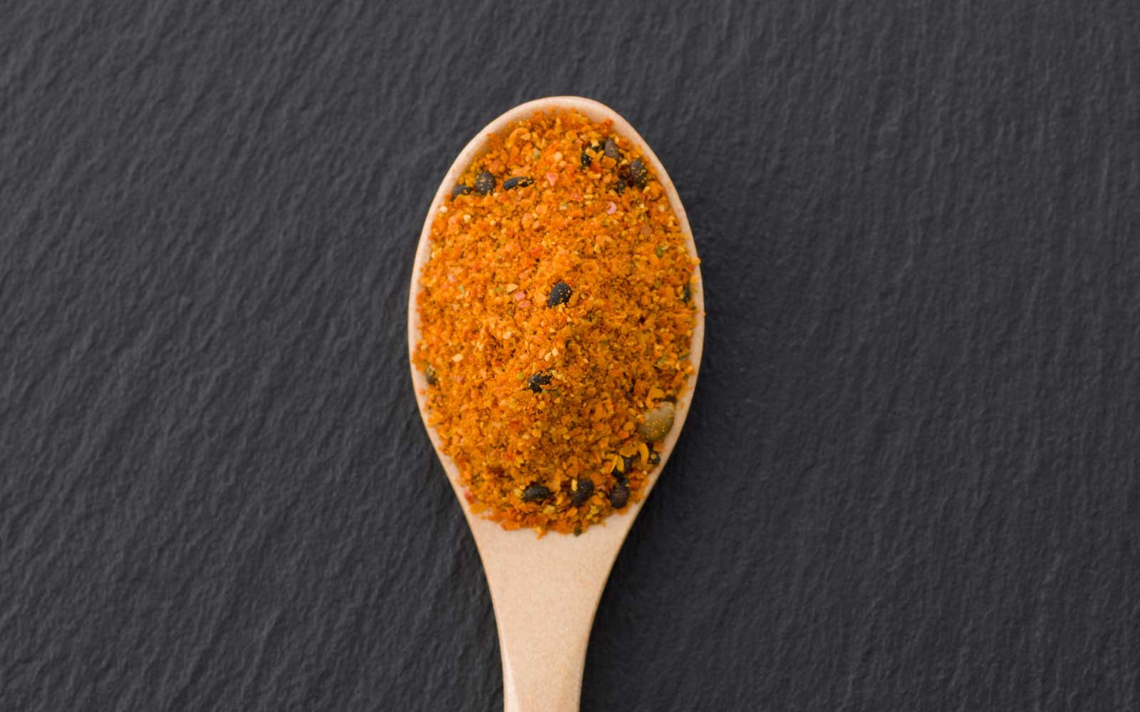 Shichimi pepper in wooden spoon on black plate