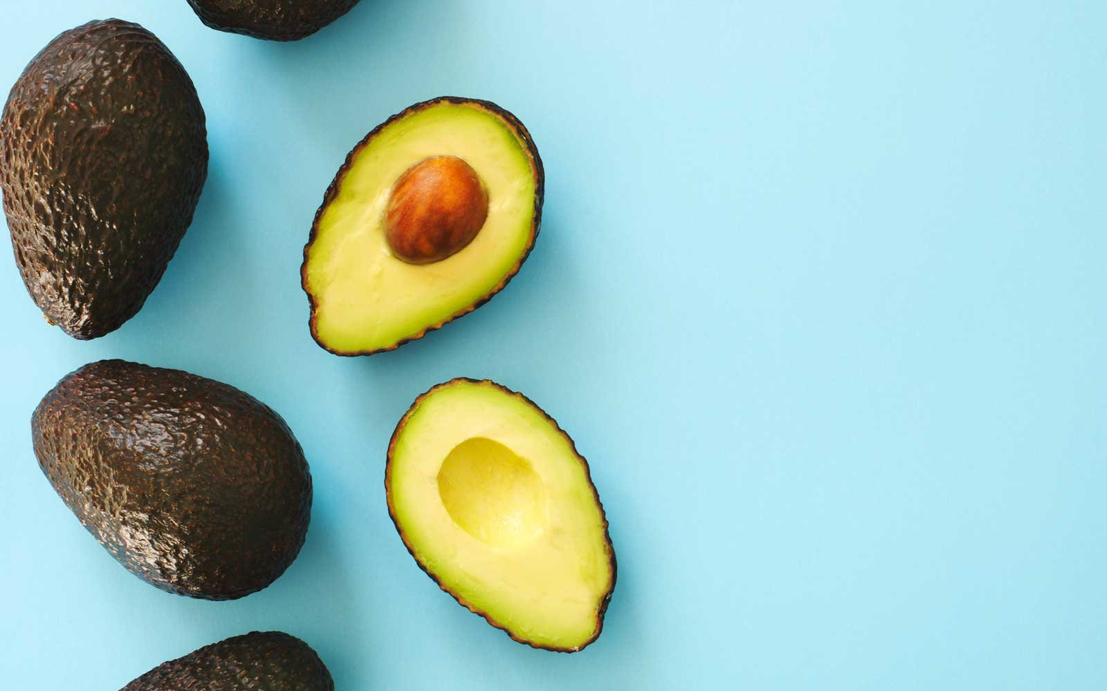 Avocado halves and whole on a blue speckle