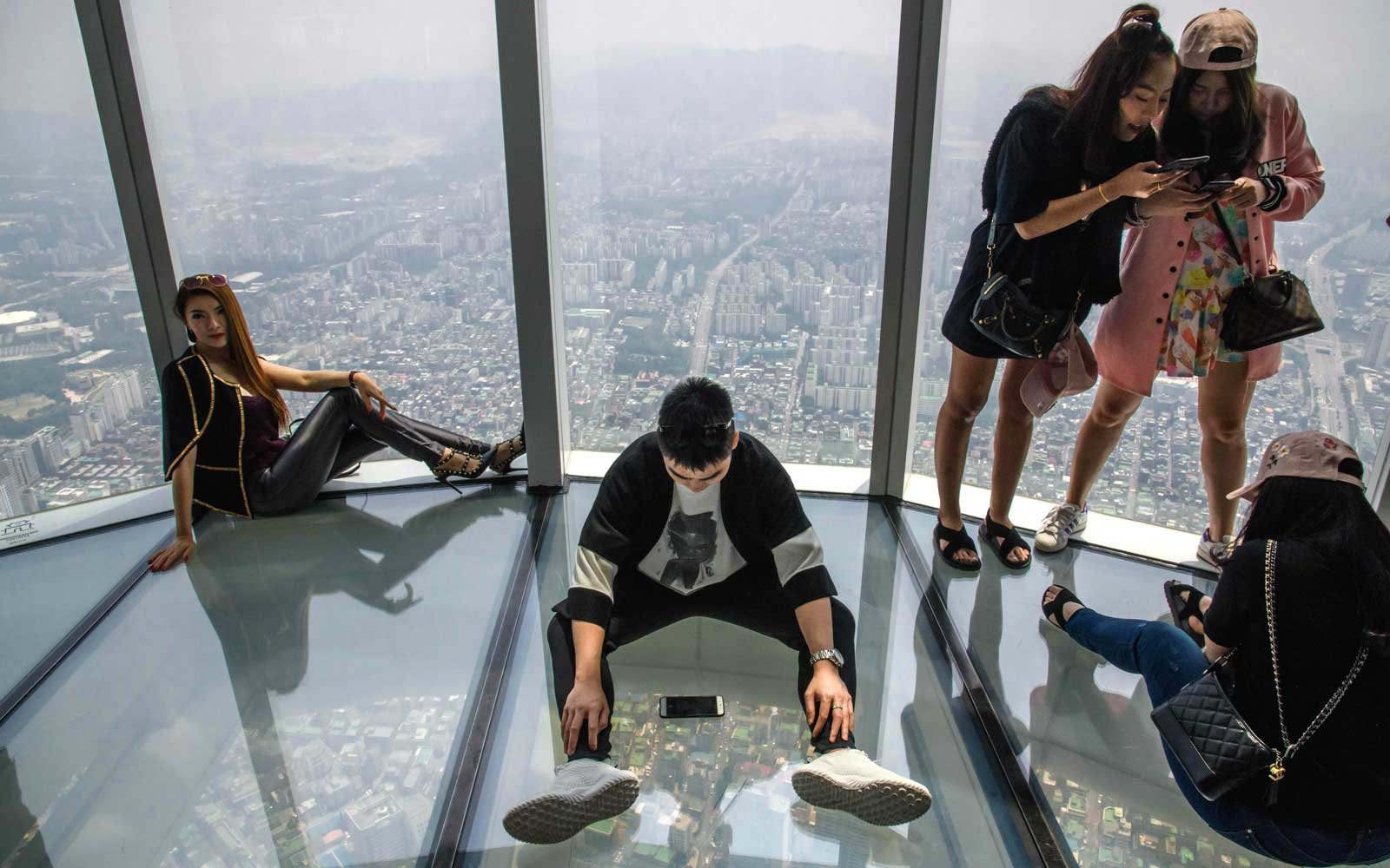 Visitors pose for photos as a viewing deck of the Lotte World Tower in Seoul on June 6, 2018