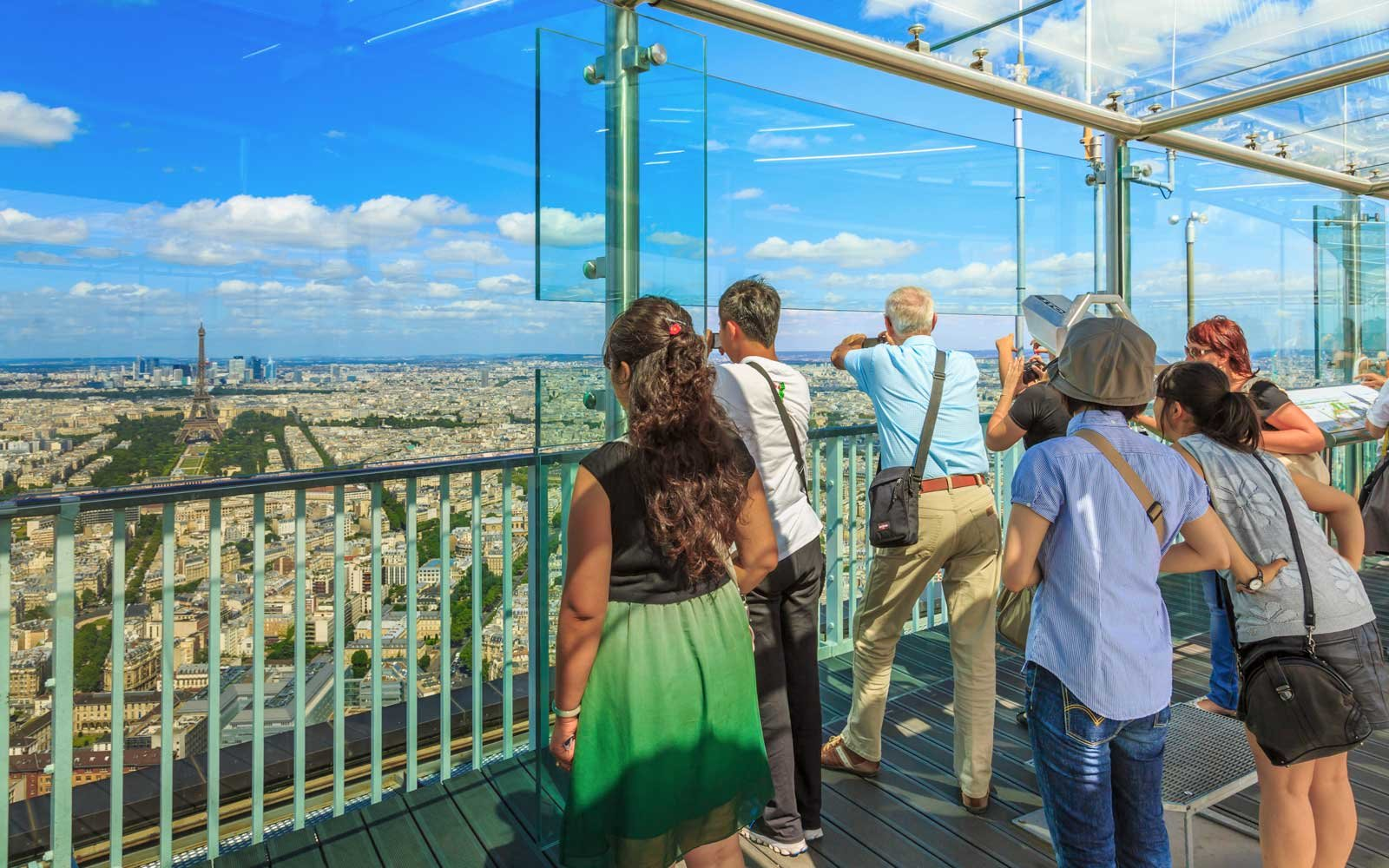 Tourists watching Paris skyline from Tour Montparnasse 56 viewing gallery, Paris, France