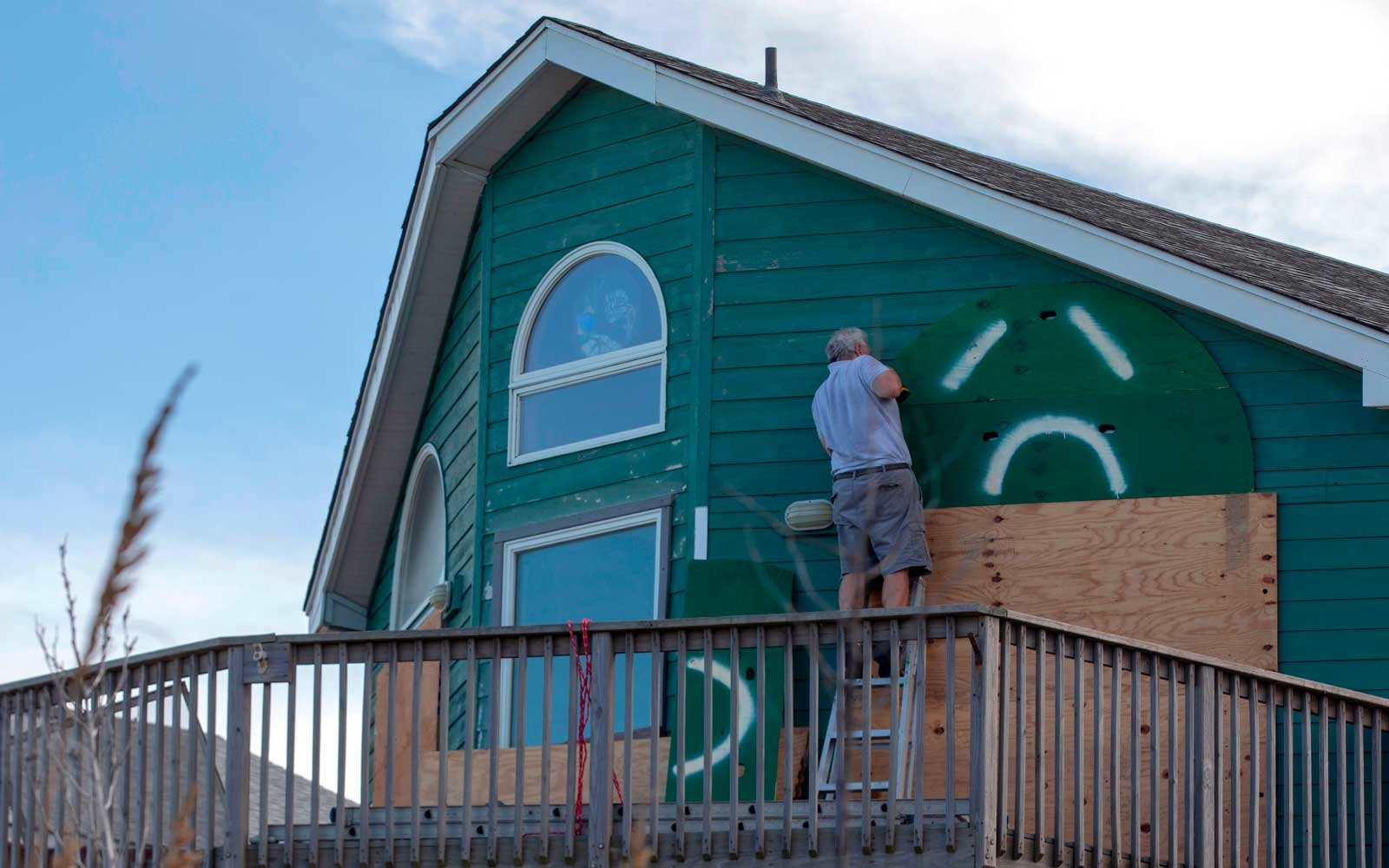 A man uses a drill to install storm shutters on a home in Kill Devil Hills in the Outer Banks of North Carolina on September 11, 2018.