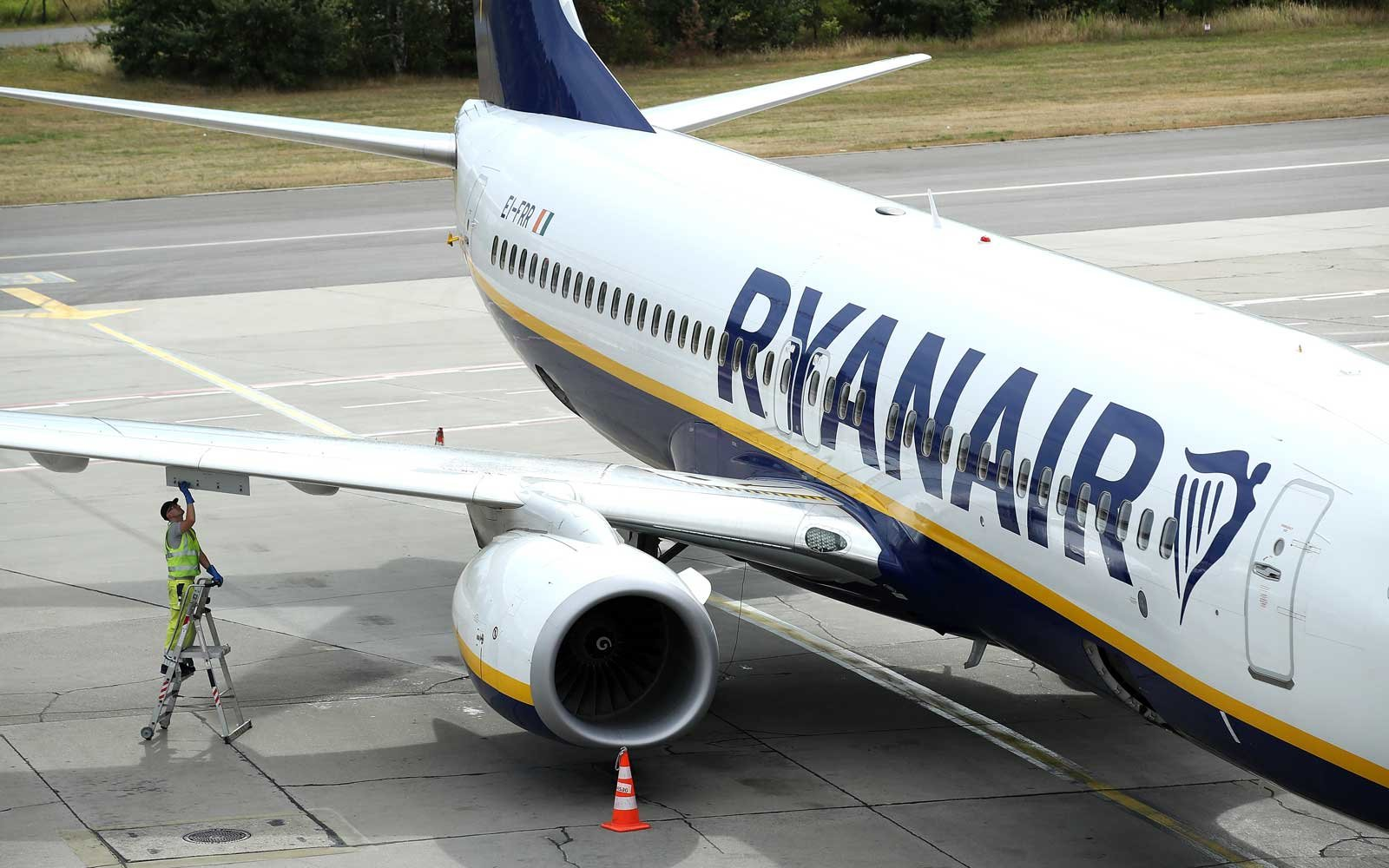 A ground crew worker stands on a ladder at a RyanAir passenger plane at Schoenefeld  Airport near Berlin during a 24-hour strike by RyanAir pilots on August 10, 2018