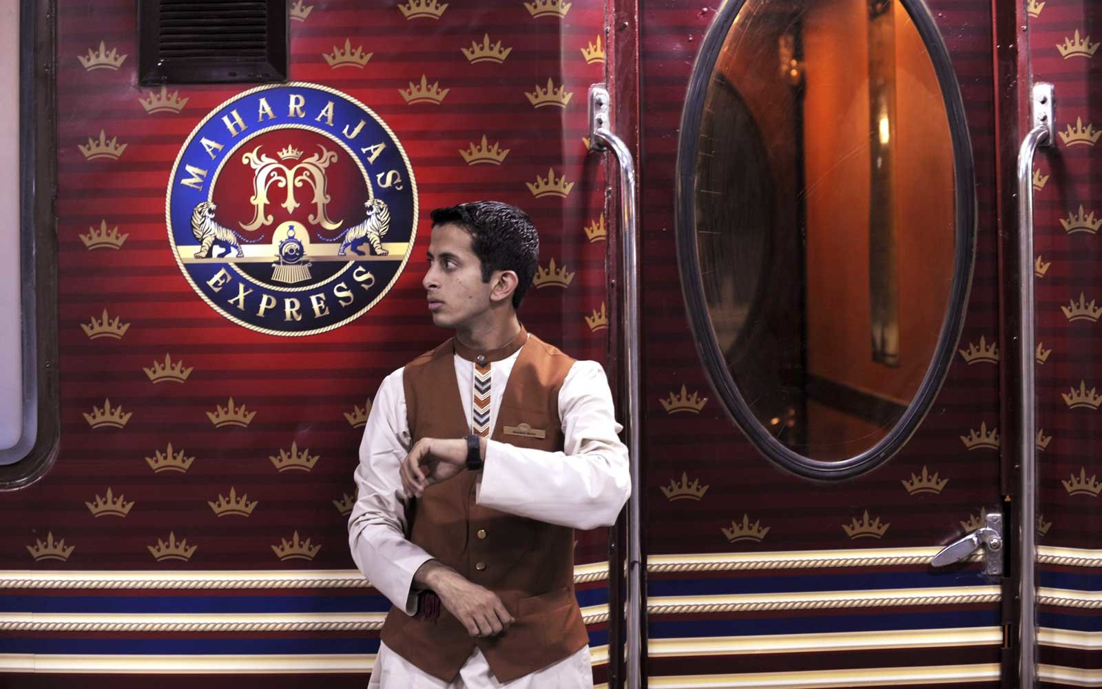 An Indian railway assistant checks his watch as he stands beside the  Maharajas' Express , India's first pan-India super luxury train, prior to its departure for Delhi from Kolkata on March 20, 2010.
