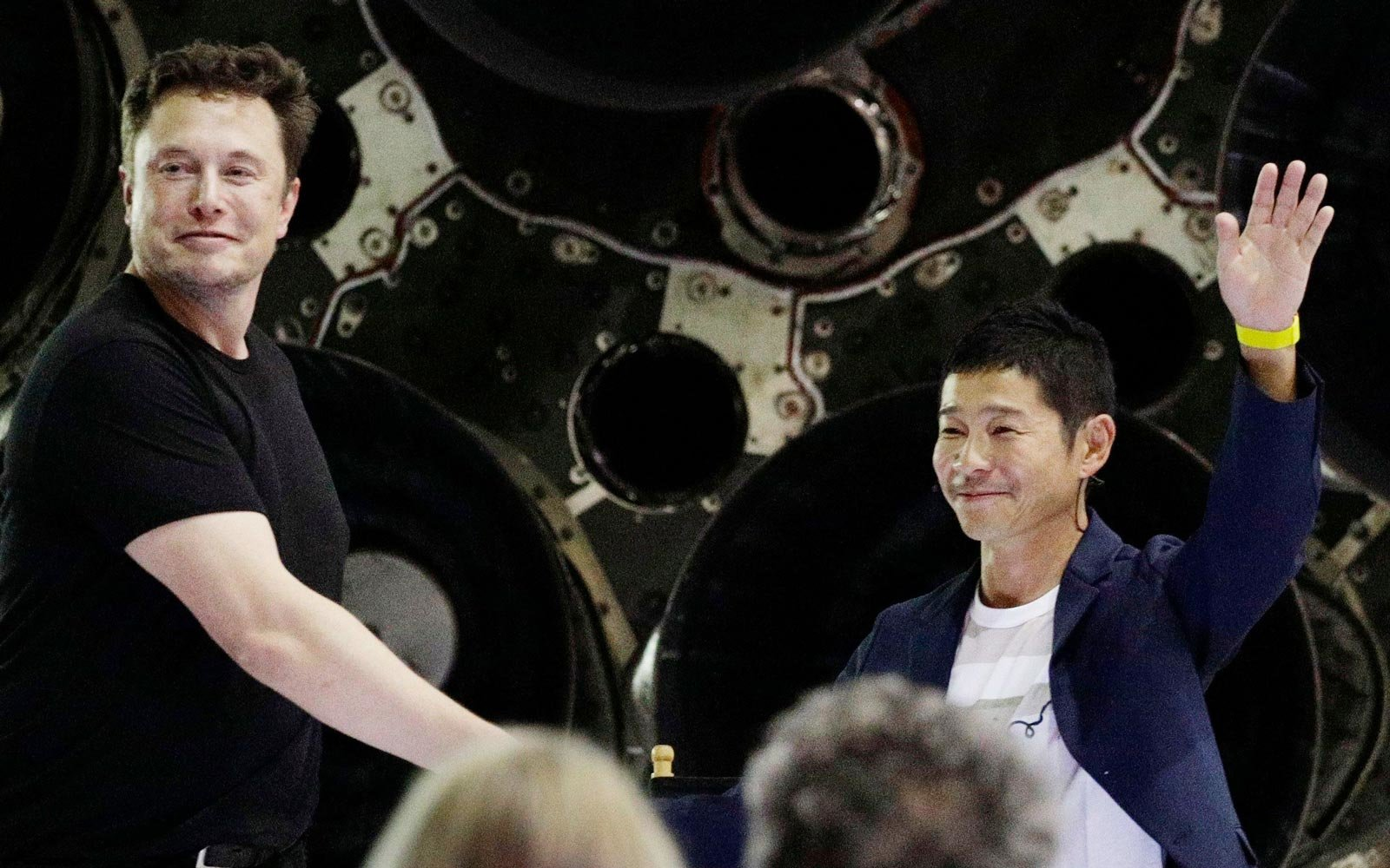 SpaceX founder and chief executive Elon Musk left shakes hands with Japanese billionaire Yusaku Maezawa right after announcing him as the first private passenger on a trip around the moon
