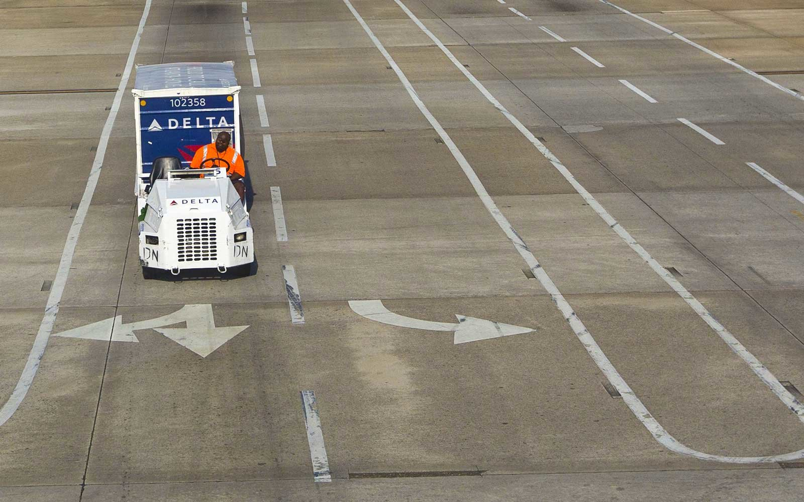A Delta airlines luggage transportation truck drives on the tarmac at the Hartsfield-Jackson Atlanta International airport