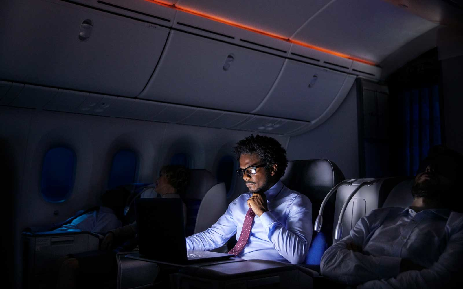 Businessman working on a laptop at night in an airplane