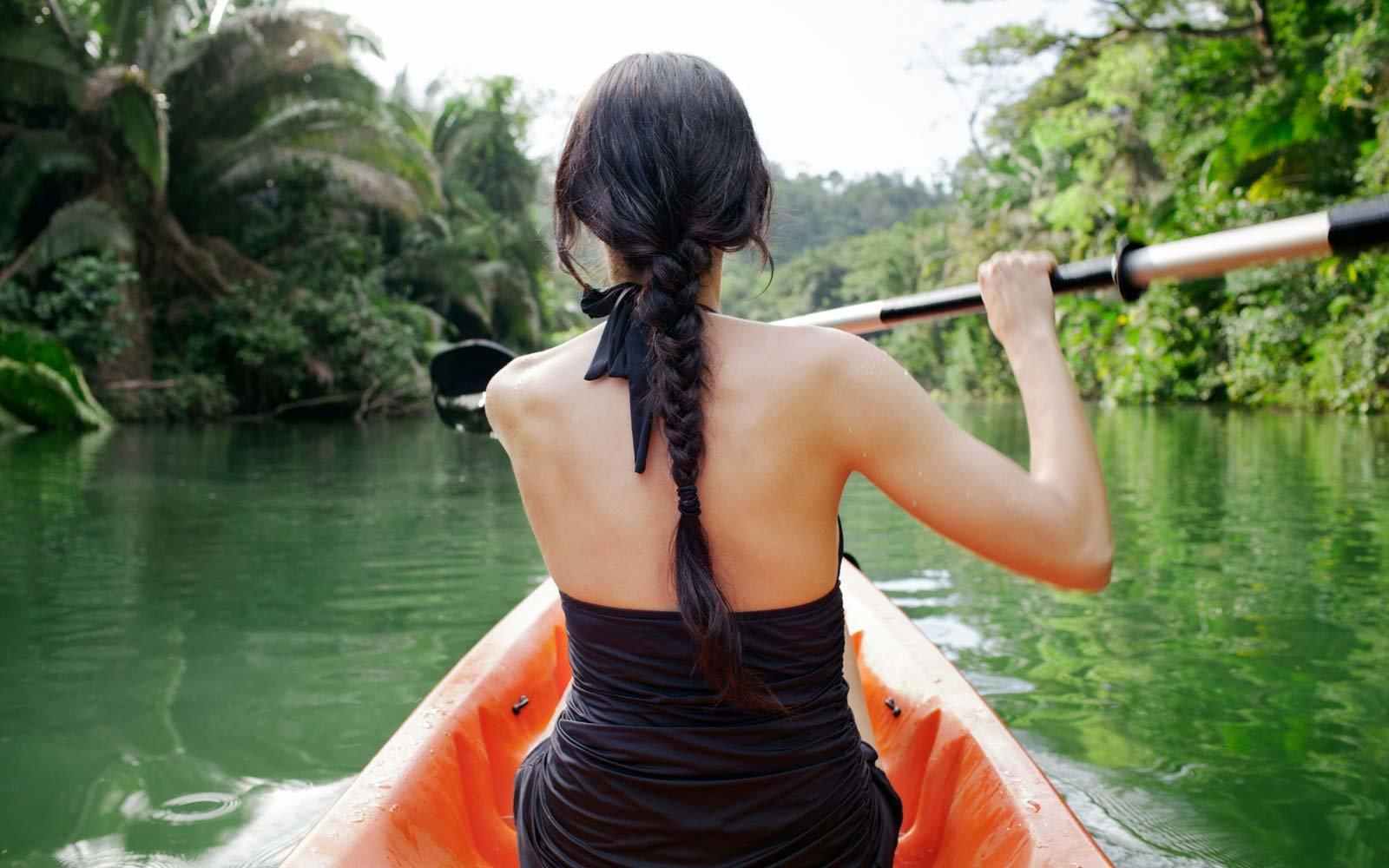 Rear view of woman kayaking on lake at forest