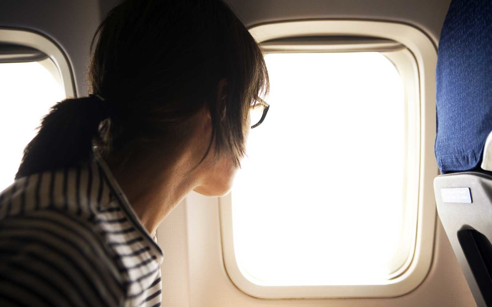 Airplane passenger looks out window
