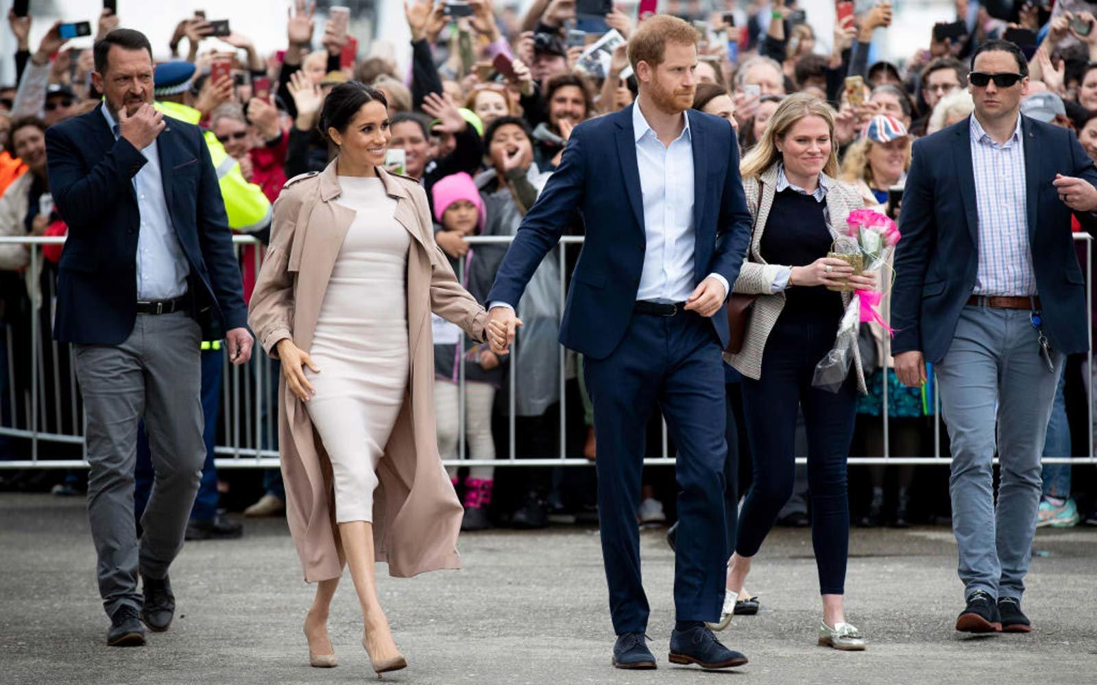 Prince Harry, Duke of Sussex and Meghan, Duchess of Sussex meet fans during a public walk along Auckland's Viaduct Harbour