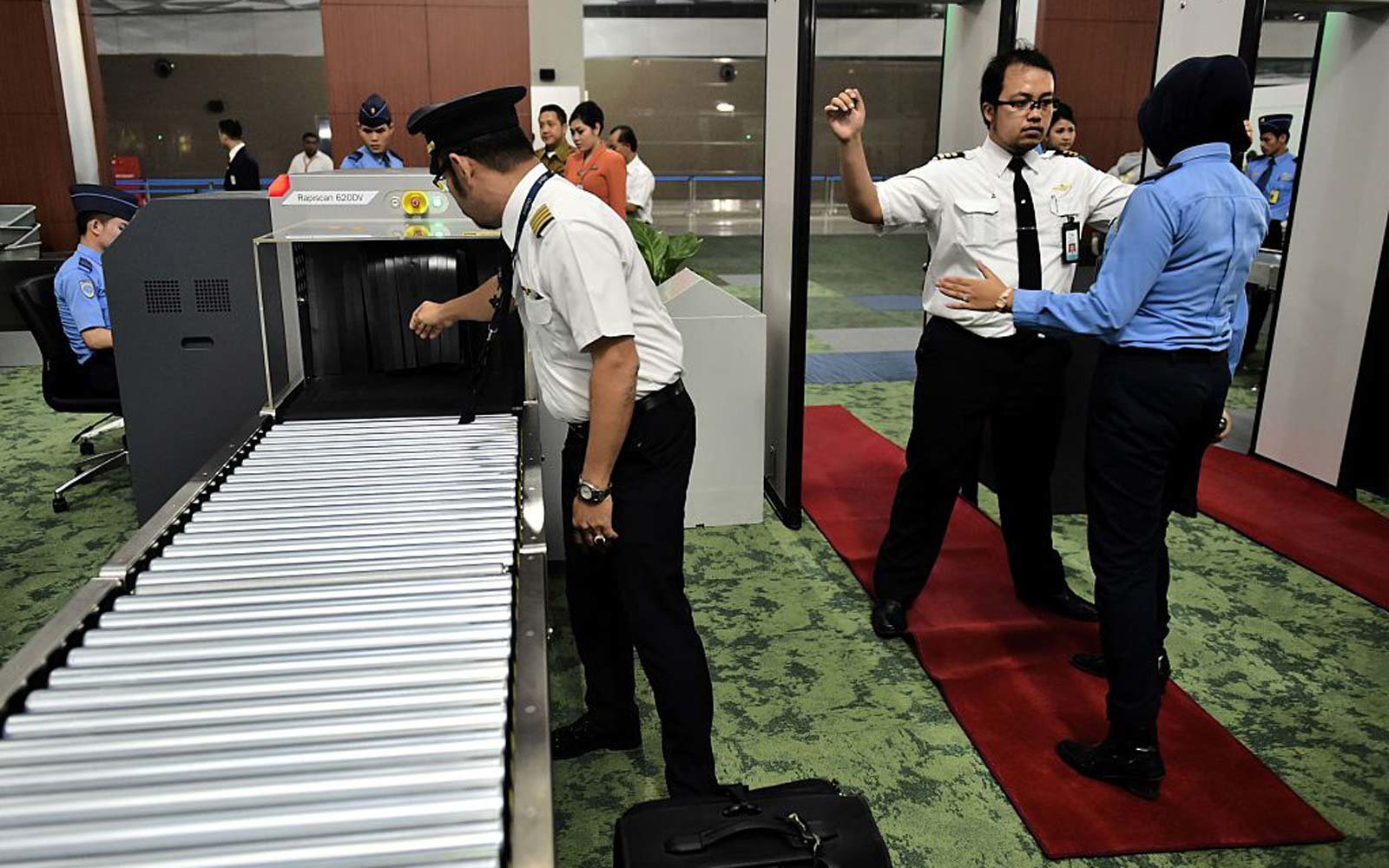 Airport personnel conduct a security check on pilots